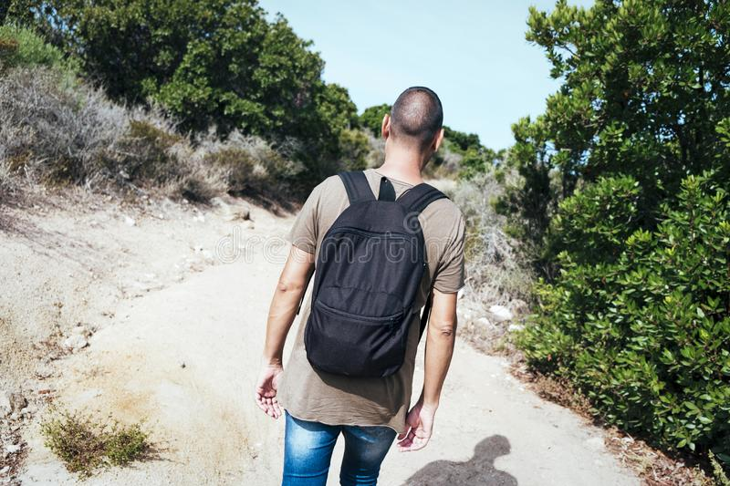 Man carrying a backpack walking by a dirt road. A young caucasian man wearing jeans and a green t-shirt, carrying a backpack, seen from behind, walking by a dirt stock images