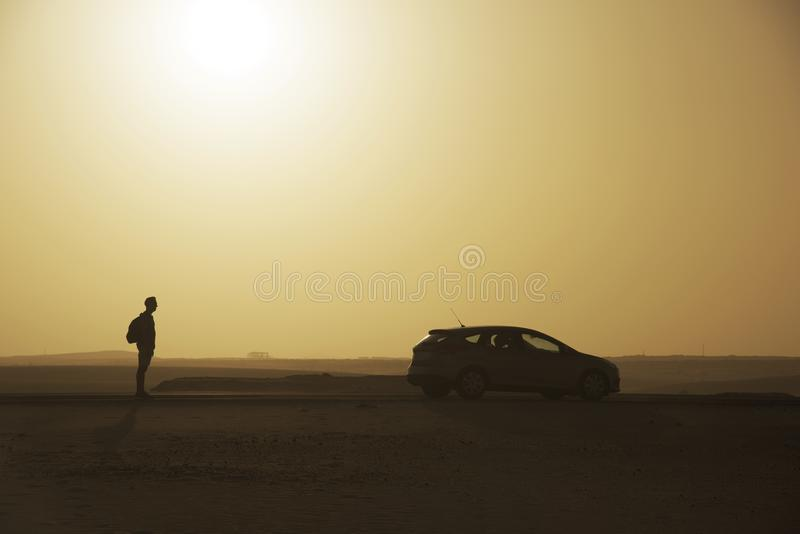 Young man in Fuerteventura, Spain. A young caucasian man, wearing shorts and carrying a backpack, standing next to a car on the road at the Corralejo dunes in stock photo