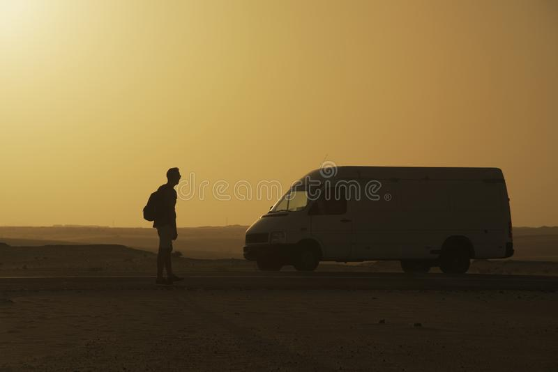 Young man in Fuerteventura, Spain. A young caucasian man, wearing shorts and carrying a backpack, standing next to a van on the road at the Corralejo dunes in stock image