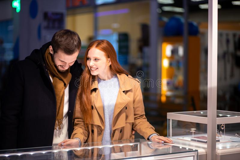 Young caucasian married couple enjoy choosing jewelry for female royalty free stock photos