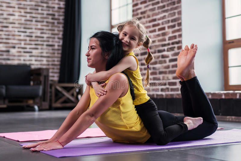 Young Caucasian mother doing yoga cobra pose on floor while her smiling daughter sitting on moms back hugging her in stock photos