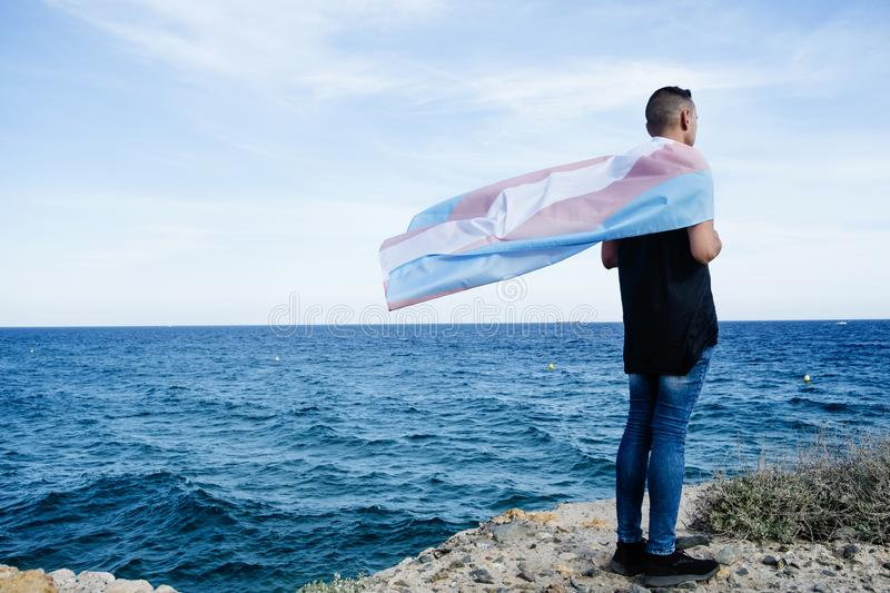 Young person with a transgender pride flag. A young caucasian person, seen from behind, draping a transgender pride flag over his or her shoulders, facing the stock images