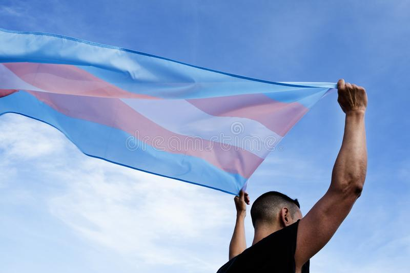 Young person with a transgender pride flag. A young caucasian person, seen from behind, holding a transgender pride flag over his or her head against the blue stock photos