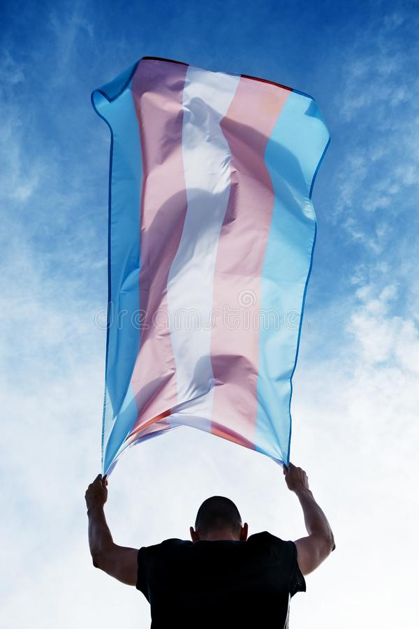 Young person with a transgender pride flag. A young caucasian person, seen from behind, holding a transgender pride flag over his or her head against the blue royalty free stock photos
