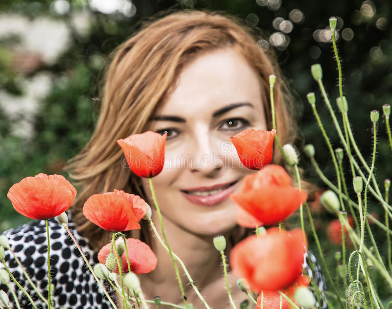 Young caucasian positive woman with corn poppy flowers, beauty a stock images