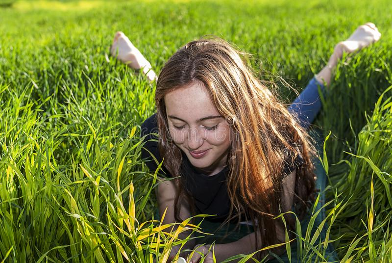Young caucasian red-haired woman, with long hair and freckles, lying on the grass royalty free stock photo