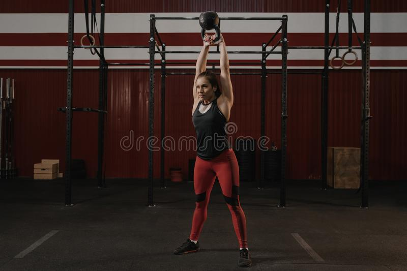 Young caucasian sports woman doing kettlebell swing exercise. As a routine of a crossfit workout stock photos