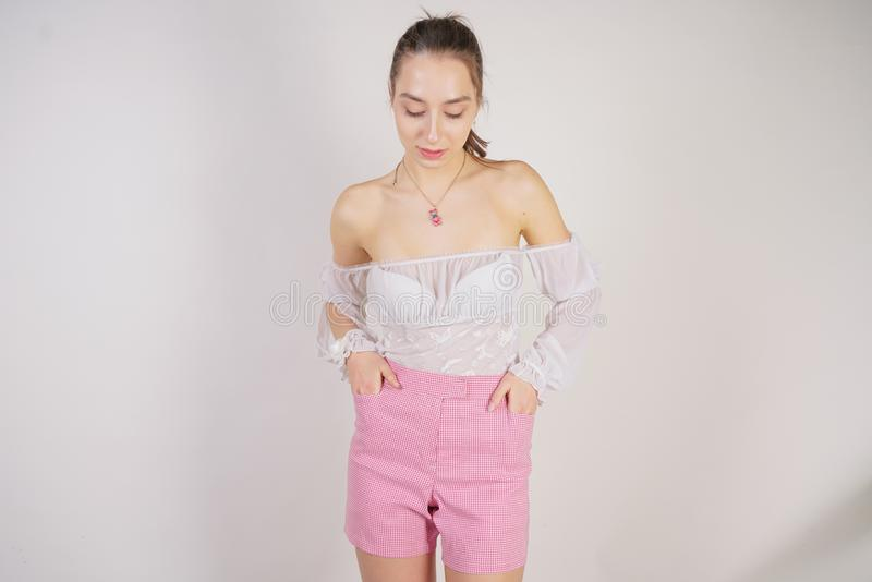 A young caucasian teen girl in a white transparent blouse and checkered pink short shorts showing summer fashion clothes and posin. G on a white background in royalty free stock photo