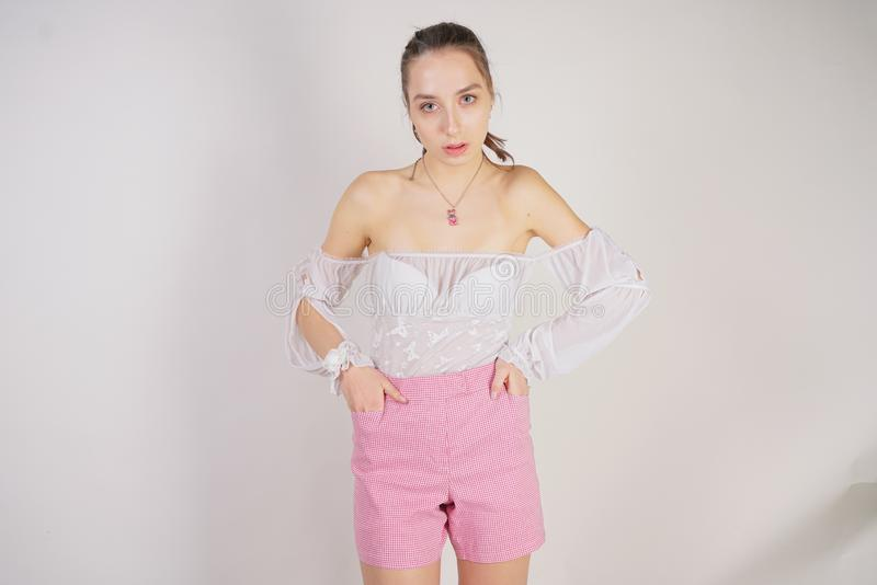 A young caucasian teen girl in a white transparent blouse and checkered pink short shorts showing summer fashion clothes and posin. G on a white background in royalty free stock photography