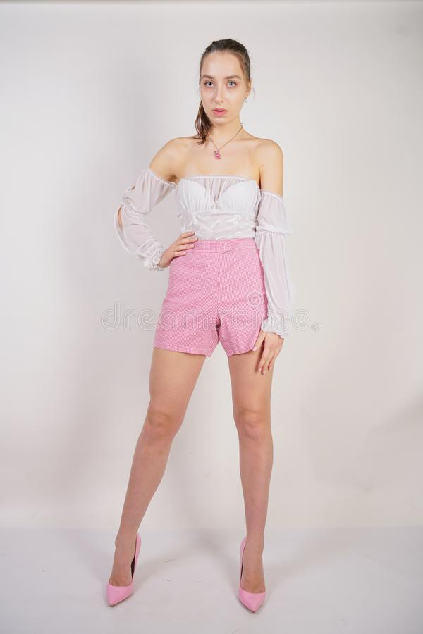 A young caucasian teen girl in a white transparent blouse and checkered pink short shorts showing summer fashion clothes and posin. G on a white background in royalty free stock images