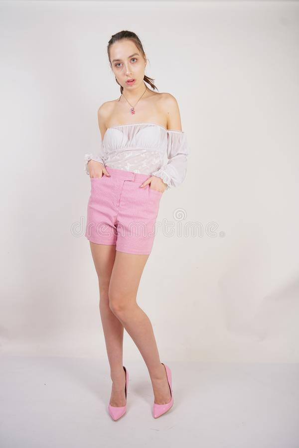 A young caucasian teen girl in a white transparent blouse and checkered pink short shorts showing summer fashion clothes and posin. G on a white background in royalty free stock image
