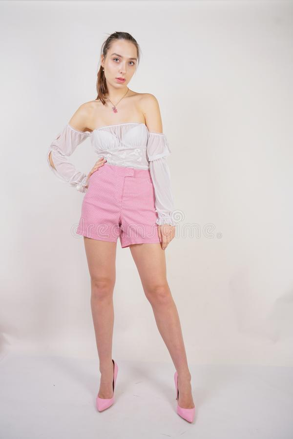 A young caucasian teen girl in a white transparent blouse and checkered pink short shorts showing summer fashion clothes and posin. G on a white background in stock images