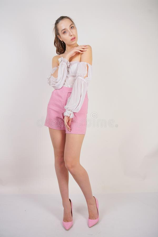 A young caucasian teen girl in a white transparent blouse and checkered pink short shorts showing summer fashion clothes and posin. G on a white background in stock photo