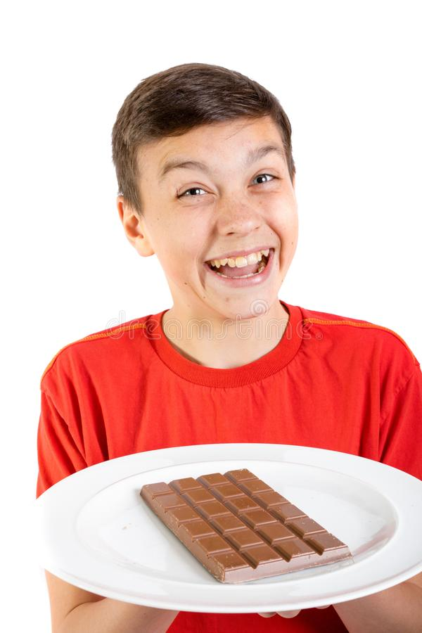 Young caucasian teenage boy with a bar of chocolate royalty free stock image