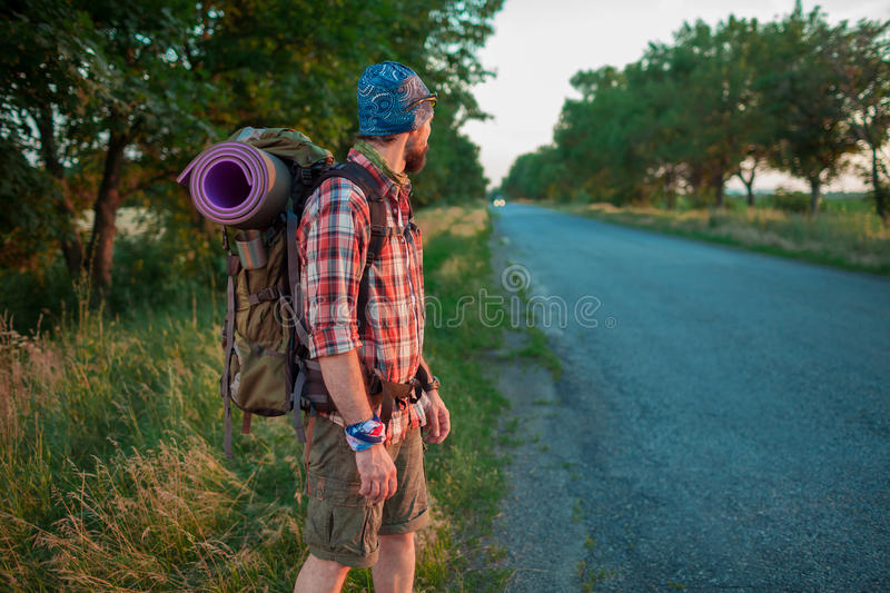 Young caucasian tourist hitchhiking along a road. Young caucasian tourist with backpack hitchhiking along a road in sunset royalty free stock photos