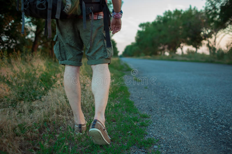 Young caucasian tourist hitchhiking along a road. Young caucasian tourist with backpack hitchhiking along a road in sunset stock photo