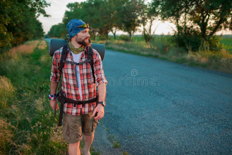 Young caucasian tourist hitchhiking along a road. Young caucasian tourist with backpack hitchhiking along a road in sunset stock image