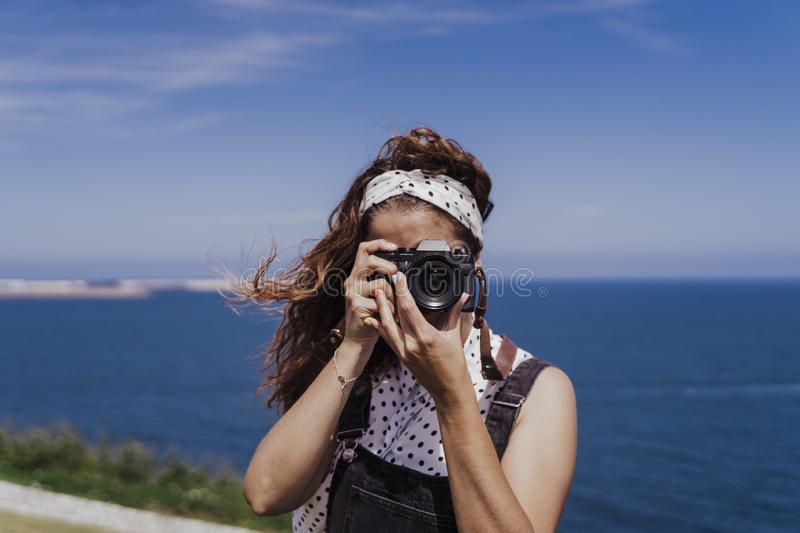 Young caucasian tourist woman outdoors taking pictures with a reflex camera on a windy and sunny day. Lifestyle, travel and royalty free stock image