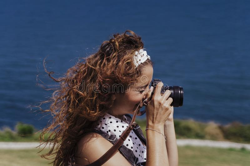 Young caucasian tourist woman outdoors taking pictures with a reflex camera on a windy and sunny day. Lifestyle, travel and royalty free stock photo