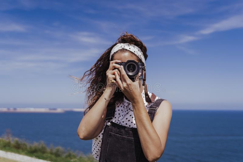 Young caucasian tourist woman outdoors taking pictures with a reflex camera on a windy and sunny day. Lifestyle, travel and royalty free stock photography