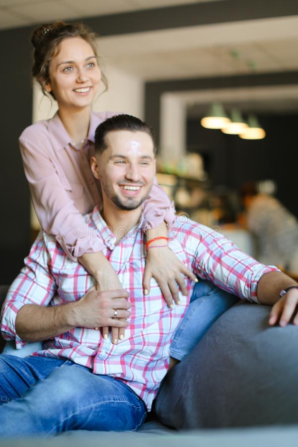 Young caucasian wife hugging husband at home. Concept of happy couple, relationship and love stock images