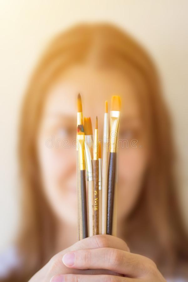 Young caucasian woman artist painter in white shirt holds in stretched hands bunch of different types of paint brushes. Arts royalty free stock photography