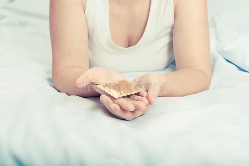 Young caucasian woman on bed gives a condom. stock image