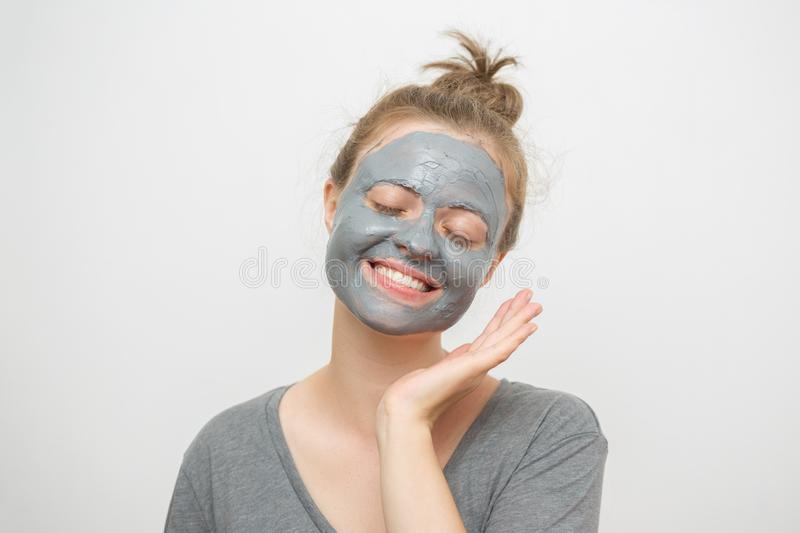 Young caucasian woman with black or grey facial clay mask on her face, smiling stock photography