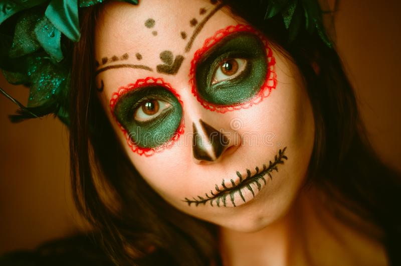 Young caucasian woman in catrina calavera style makeup horizontal portrait close up face. Young caucasian woman in catrina calavera style makeup and blue flower royalty free stock photography