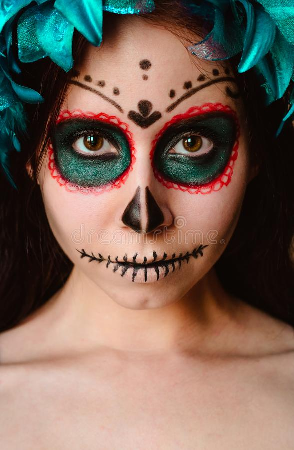 Young caucasian woman in catrina calavera style makeup vertical portrait close up face. Young caucasian woman in catrina calavera style makeup and blue flower royalty free stock photography