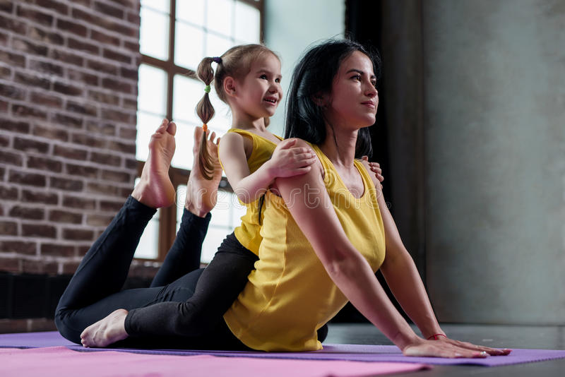 Young Caucasian woman doing stretching exercise for spine together with a child sitting on her back in gym stock photos