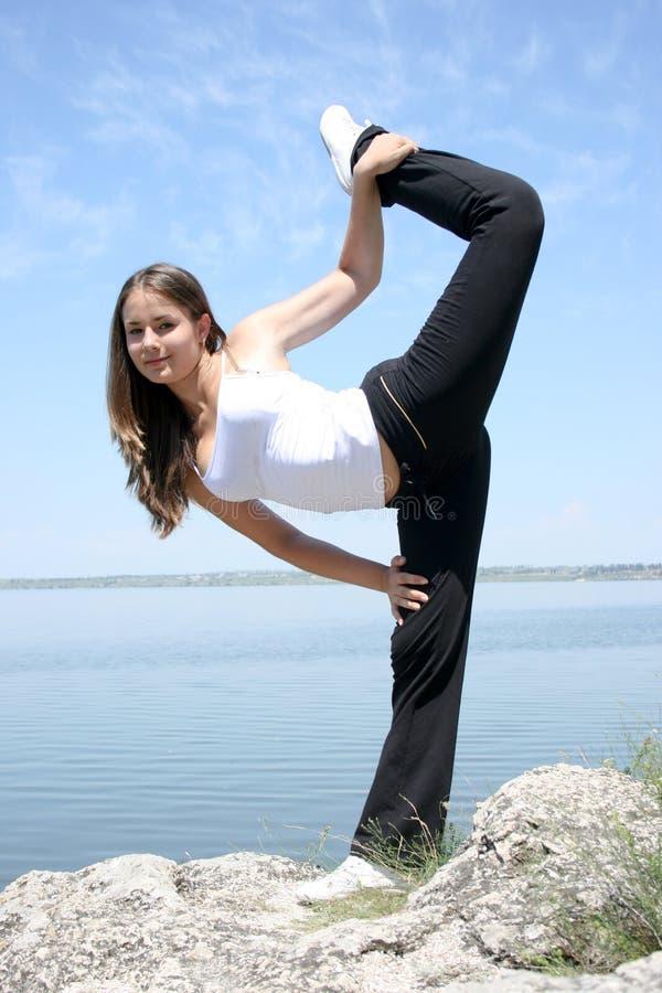 Young caucasian woman doing yoga exercises stock photography