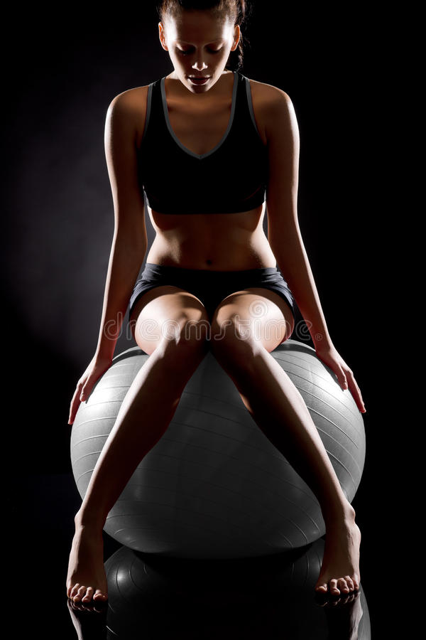 Young Caucasian woman exercising on fitness ball royalty free stock photos