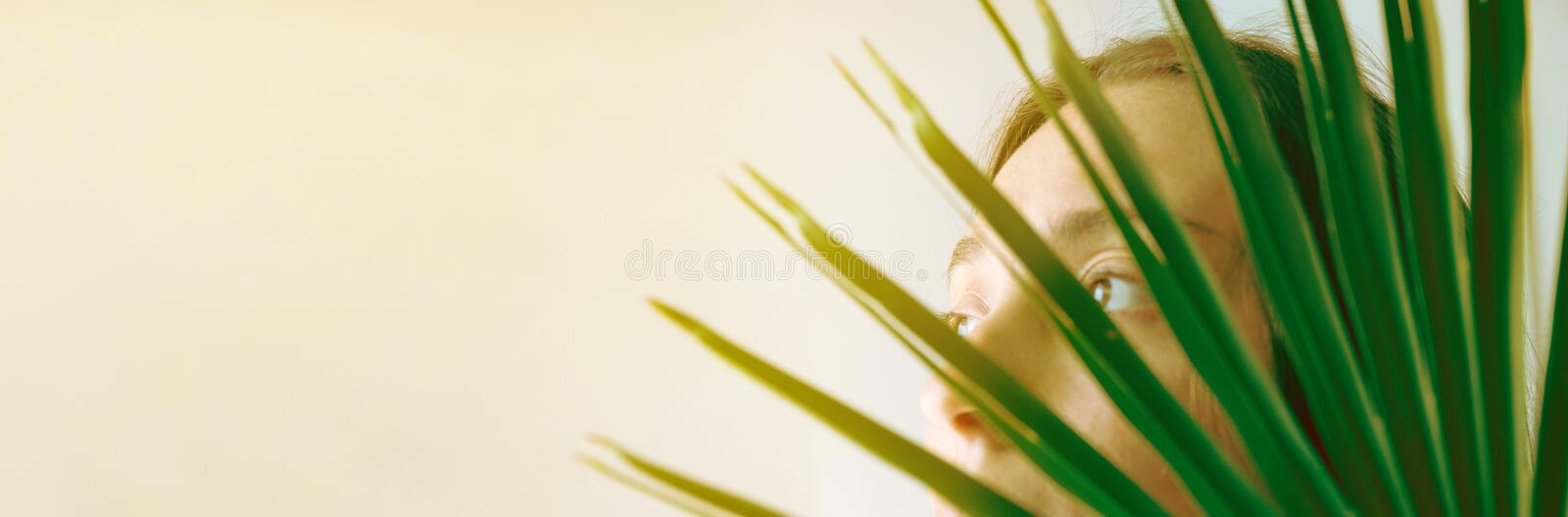 Young caucasian woman female behind green palm leaf girl looks in the window. Bright morning sunlight. Houseplants plant lady royalty free stock photography