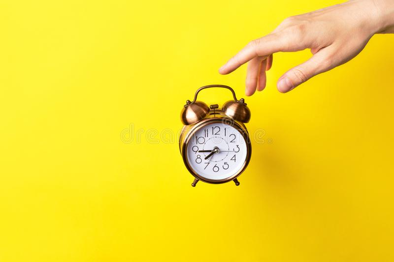Young caucasian woman girl hand pointing at floating alarm clock turning it off. Bright sunny background. Energy time management. Young caucasian woman girl hand stock photo