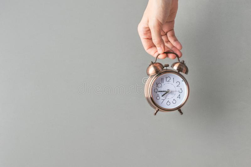 Young Caucasian woman girl holds in hand alarm clock on gray wall background. Waking up energy self-organization time change. Young Caucasian woman girl holds in royalty free stock images