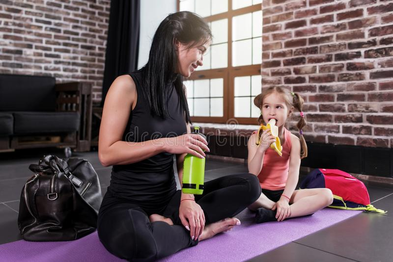 Young Caucasian woman and a happy girl child relaxing after yoga training sitting on mat with legs crossed drinking stock photo