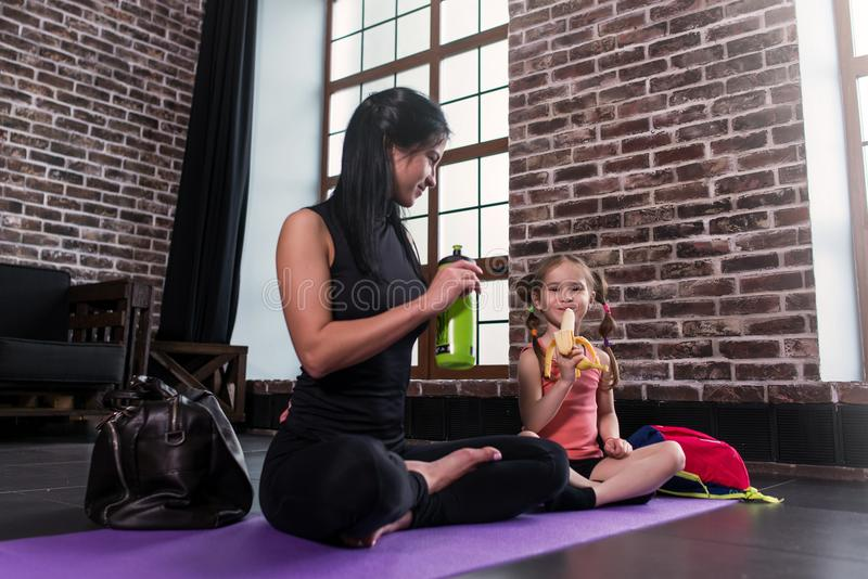 Young Caucasian woman and a happy girl child relaxing after yoga training sitting on mat with legs crossed drinking royalty free stock images