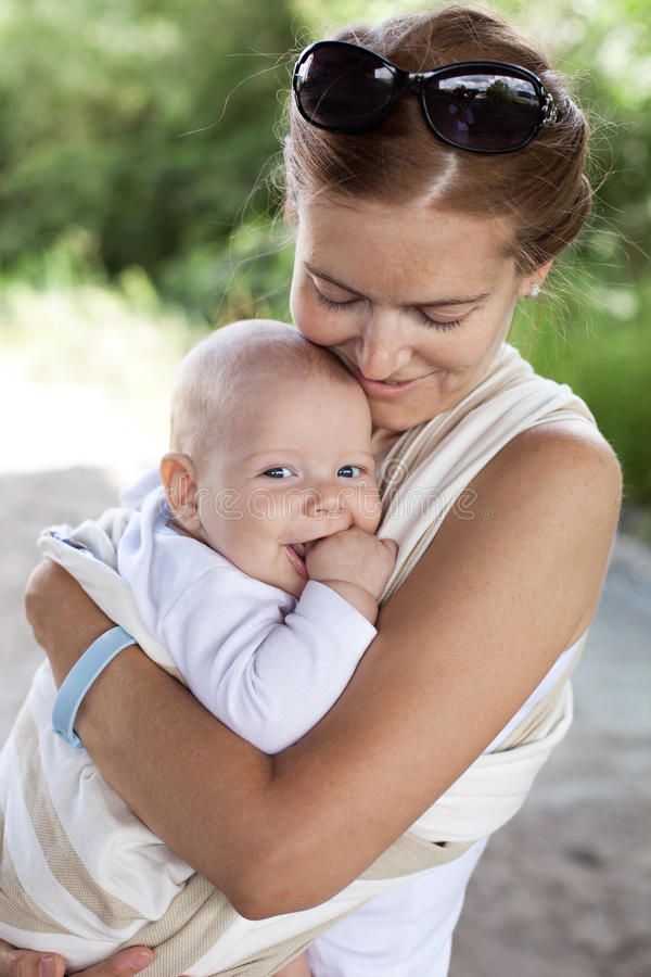 Young Caucasian woman and her baby son in sling royalty free stock images