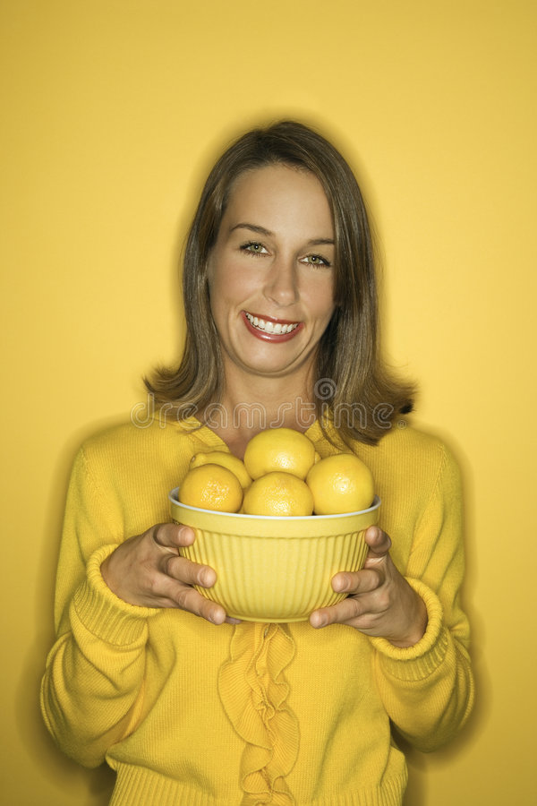 Young Caucasian woman holding bowl of lemons. Portrait of smiling young adult Caucasian woman on yellow background holding bowl of lemons royalty free stock image