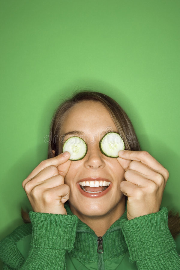 Young Caucasian woman holding cucumber slices over her eyes. stock image