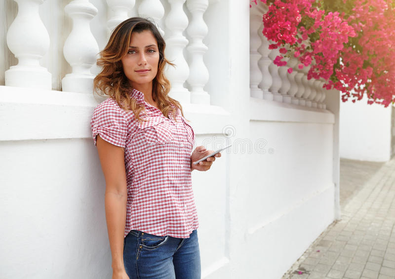 Young caucasian woman holding mobile phone. Young caucasian woman in red shirt holding mobile phone while looking at the camera - copy space stock images