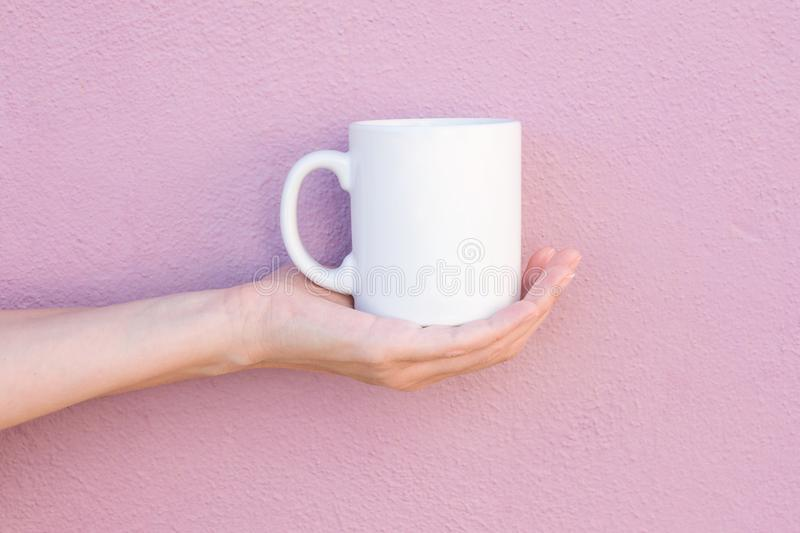 Young Caucasian Woman Holds on Hand Palm Blank Mockup White Mug on Light Pink Painted Wall. Airy Breezy Style. Template for Text Artwork Lettering. Trendy royalty free stock photography