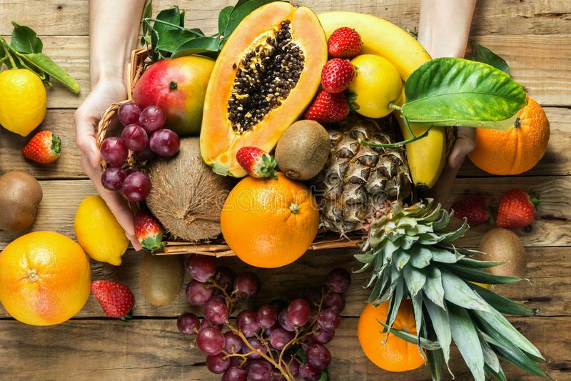 Young caucasian woman holds in hands box with raw organic tropical and seasonal summer fruits berries. Halved papaya coconut mango royalty free stock image