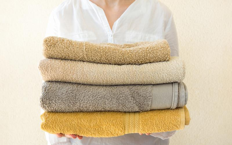 Young caucasian woman holds in hands stack of clean folded terry towels. White wall background. Laundry spa wellness cleanliness royalty free stock photo