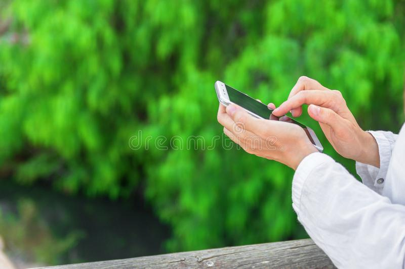 Young caucasian woman holds white smartphone touching screen texting reading on green foliage background. Modern technology. Communication concept. Authentic stock photography