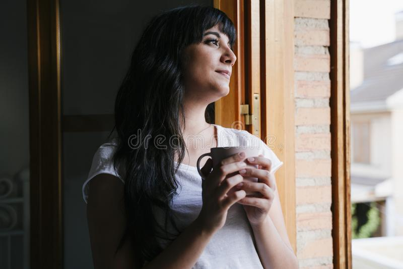 Young caucasian woman at home by the window having a cup of coffee or tea. Morning and relax concept. Lifestyle indoors stock photography