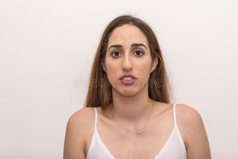 Young Caucasian woman looks at us with fear and worry stock photography