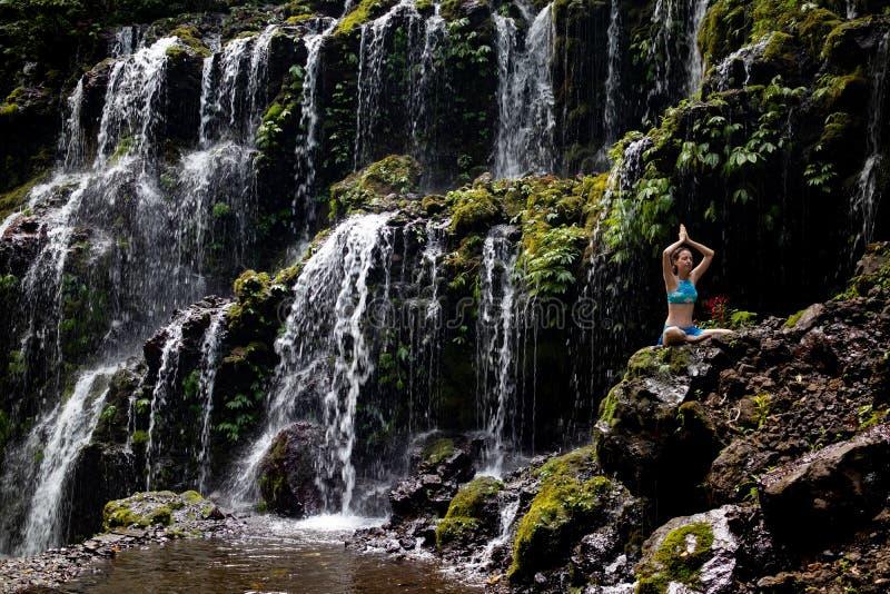 Young Caucasian woman meditating, practicing yoga at waterfall. Namaste mudra. Banyu Wana Amertha waterfall Wanagiri, Bali, stock image