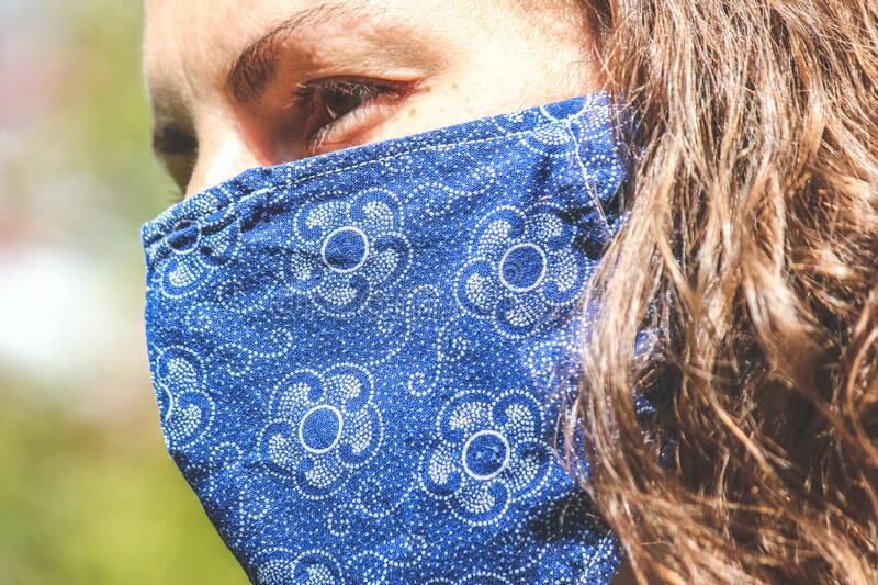 Young Caucasian woman outdoors with a blue fabric face mask during coronavirus pandemic. Coronavirus, COVID-19 outbreak. Virus. Protection concept. Blurred royalty free stock image